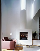 Pink armchair in front of a fire in a fireplace in an open, minimalist living room