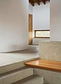 Treppe und Sitzbank aus Stein mit Holzauflage im Vorraum