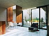 Wohnraum mit weissen Stühlen am originellen Esstisch vor Fensterfront
