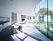 New home with a curved design with open living-dining area in front of a glass facade