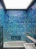 Bathroom with assorted blue mosaic tiles and bathtub under an illuminated ceiling