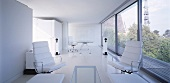 White living-dining room with white leather armchairs in front of a wall of windows