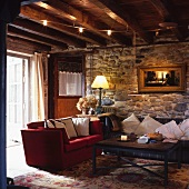 Old, living room in a country home with red couch and a sofa decorated with pillows in front of a natural stone wall