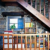 Wooden stairway above a mini-library on a natural stone wall of a country home