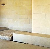 Light colored stone block in front of wall with stone tiles