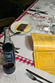 A menu, red wine and dessert on a table in a restaurant