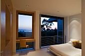 Double bed in a contemporary bedroom with open French window
