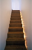 Wooden stairway with floor lighting at the side in a narrow stairwell