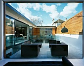 View through a bank of windows onto dark, cubic-shaped patio furniture in front of a pool in a contemporary courtyard