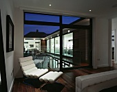 Modern, white leather lounger with foot rest in front of a terrace window and a view of a pool in the evening light