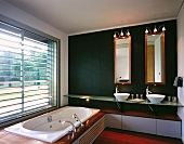 Designer bathroom with the tub built into a platform in front of a window and vanity on a dark wall