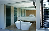 Open sliding doors and a view of a free standing bathtub fixture in front of a white vanit