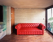 Brick-red leather sofa in front of a concrete wall next to a terrace window