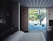 Bedroom with open terrace door and view of a gnarled tree in a courtyard
