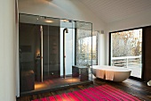 Freestanding bathtub in front of terrace windows next to a spacious glass shower stall with pink striped rug