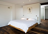 A double bed in front of a white partition wall in a bedroom with dark, rustic parquet