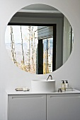 A white designer wash stand with a cupboard underneath and a round wall mirror
