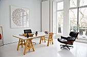 Arbeitstisch auf Holzböcken und Sessel aus Bauhauszeit im minimalistischen eleganten Raum