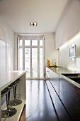 A narrow designer kitchen with a white counter in front of the cupboards