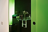 A view into an open-plan bathroom with bathing utensils on a shelf and a green glass wall