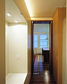 A classic-modern corridor with an illuminated cloakroom niche and a view through a glazed door into the kitchen