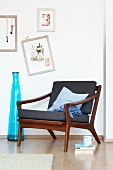 60s armchair in Danish design next to a blue floor vase and pictures on the wall