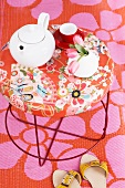 A teapot and a teacup on a Moroso table with a floral pattern