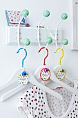 Coat hangers decorated with buttons, ribbon and name tags hanging on a wall mounted coat rack