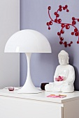 A white table lamp by Lous Poulsen or Verner Panton and a Buddha figure on a chest of drawers in front of a wall decoration