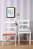 Vintage chairs upholstered with new fabric in front of striped wall paper