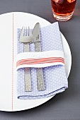 A spotted napkin with cutlery and a ribbon