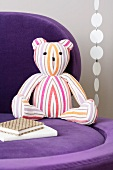 A striped teddy bear on a purple chair