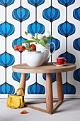 White teapot with tulips on a small table in front of vintage wallpaper decorated with an onion pattern