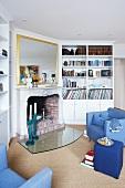 Blick in ein Wohnzimmer mit blaeun Sitzmöbeln, Bücherschrank und Kamin