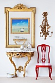 Rococo wall table and a red chair with a picture in a gold frame and a wall candle holder above