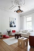 White living room suite and side tables in a living room with stucco ceiling