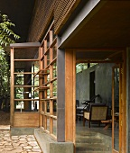 Traditional Indian house with wood and glass facade and open door with view into terrace