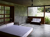 Purist concrete bedroom with double bed and white bed linen