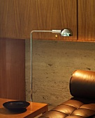 Detail of retro chrome standard lamp next to brown leather couch