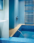 Light blue modern bathroom and full bathtub with running water