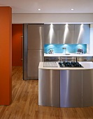 Kitchen island with stainless steel fronts in open-plan designer kitchen