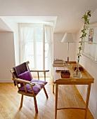 Rustikaler Armlehnstuhl aus Holz vor schlichtem Sekretär im Dachzimmer