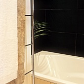 Detail of a corner of a bathroom with a bath tub and black tiles on the wall