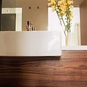 A modern white wash basin and walnut panelling