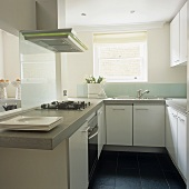 A functional white kitchen with an extractor fan above a work surface