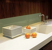 Stacks of plates and onions on a white work surface with an integrated sink