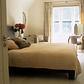 A view through an open door onto a double bed with a white quilt and a dressing table in the corner