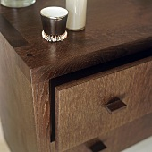 A decorative porcelain cup on a chest of drawers made of dark wood
