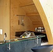 A glass-topped bar and a kitchen built into a wooden niche