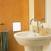 A designer wash basin with stainless steel taps and a mirror